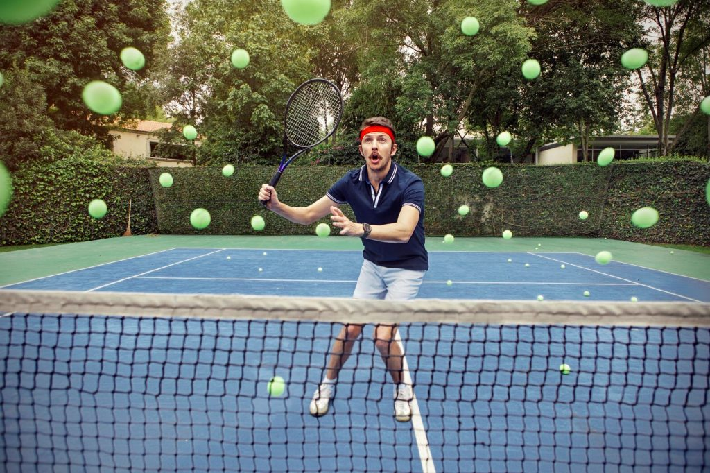 Tennis player struggling to hit lots of tennis balls