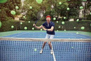 Tennis player struggling to hit lots of tennis balls